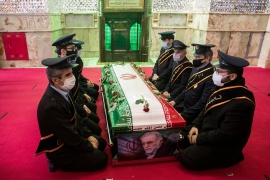 Mourners sit next to the coffin of nuclear scientist Mohsen Fakhrizadeh during the burial ceremony at the shrine of Imamzadeh Saleh in Tehran [File: Reuters]