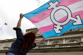A person holds up a flag during a rally to protest against the Trump administration's reported transgender proposal to narrow the definition of gender to male or female at birth, October 24, 2018 [File: Brendan McDermid/Reuters]