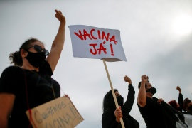 A demonstrator holds a banner reading ''vaccine now'' during a rally honouring COVID-19 victims and demanding vaccines in Brasilia, Brazil [Adriano Machado/Reuters]