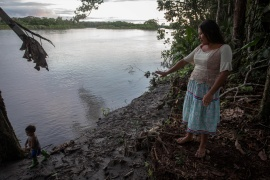 Fanny Licuy gestures to the river banks after oil spill hit her community in Sani Isla, Ecuador on May 9, 2020 [File: Ivan Castaneira/Amazon Watch/Handout via Reuters]