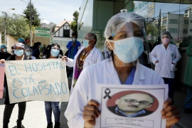 Medical workers hold a sign that reads 'The hospital is collapsed' as they attend a protest demanding a rigid quarantine, in La Paz, on January 27, 2021 [David Mercado/Reuters]