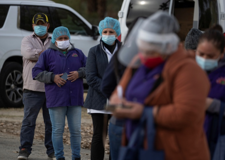 Farmworkers line up to receive COVID-19 vaccinations in Mecca, California on February 1 [File: Mike Blake/Reuters]