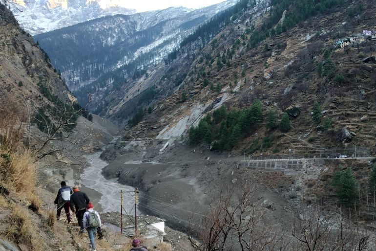 People walk past a destroyed dam after a Himalayan glacier broke and crashed into the dam at Raini Chak Lata village in Chamoli district, Uttarakhand, India [Reuters]