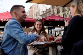 French visitors Adrien Durand (L) and Juliette Motillon (C) enjoy a meal on a terrace during their week on holiday as the COVID pandemic continues in Madrid, Spain, February 5, 2021 [Juan Medina/Reuters]