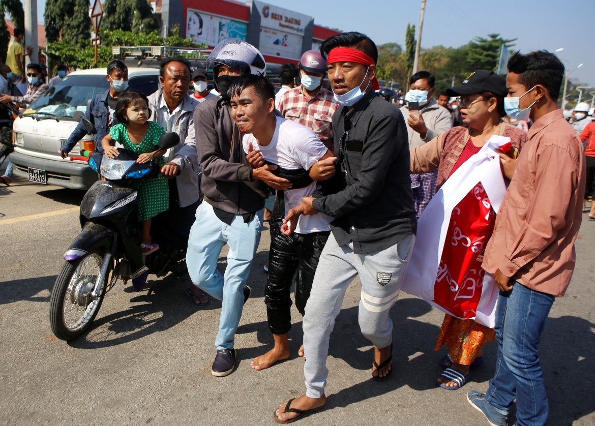 An injured protester is helped by his fellow protesters at a rally in Naypyidaw. The unrest revived memories of almost 50 years of direct army rule until the military began withdrawing from civilian politics in 2011, though it never gave up its control over the civilian government led by Aung San Suu Kyi's NLD party. [Reuters]
