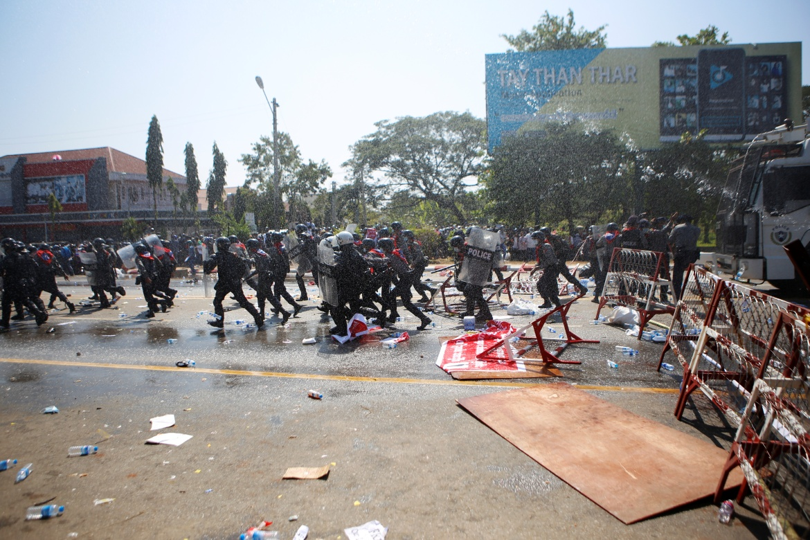 Police officers run during clashes with protestors rallying against the military coup and demanding the release of elected leader Aung San Suu Kyi, in Naypyidaw. [Reuters]