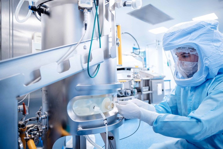 A worker is engaged in the production of the Pfizer-BioNTech COVID-19 vaccine at a recently approved facility in Marburg, some 90km north of Frankfurt, Germany on January 20, 2021 [File: BionTech/Handout via Reuters]