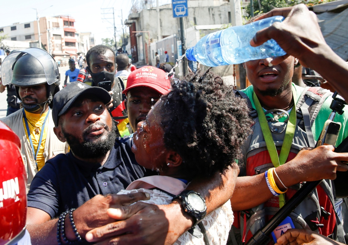 Journalists help a colleague who fainted after police fired tear gas during the protests. [Jeanty Junior Augustin/Reuters]