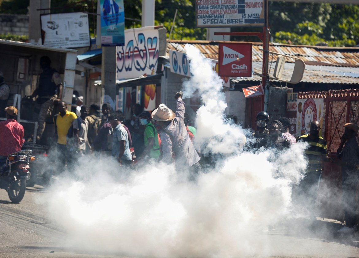 A man throws a tear gas canister back at the police during the protest in Port-au-Prince. Tensions intensified over the weekend after Moise alleged there was an attempt to overthrow his government. [Jeanty Junior Augustin/Reuters]