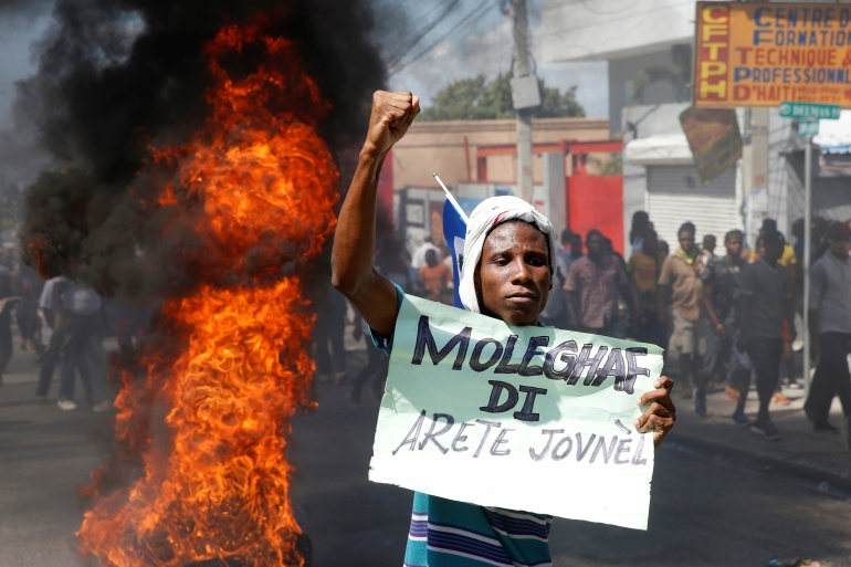 A demonstrator gestures near a barricade during a protest against Haiti's President Jovenel Moise, in Port-au-Prince, Haiti, on February 14, 2021 [Jeanty Junior Augustin/ Reuters]