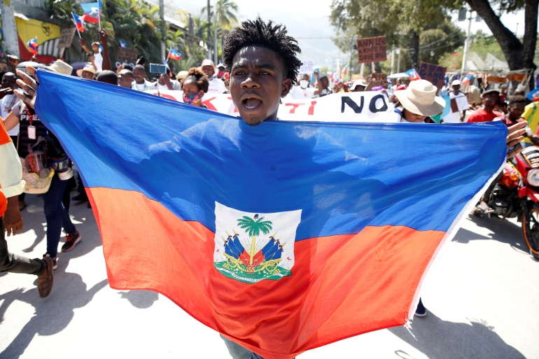 A demonstrator takes part in a protest against Haiti's President Jovenel Moise, in Port-au-Prince, on February 14 [Jeanty Junior Augustin/Reuters]