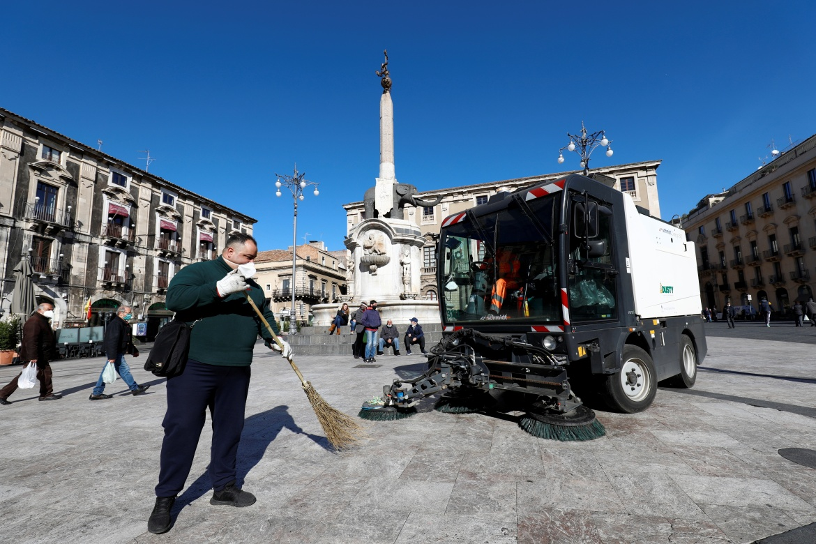 Workers clean ash from a square in Catania. [Antonio Parrinello/Reuters]
