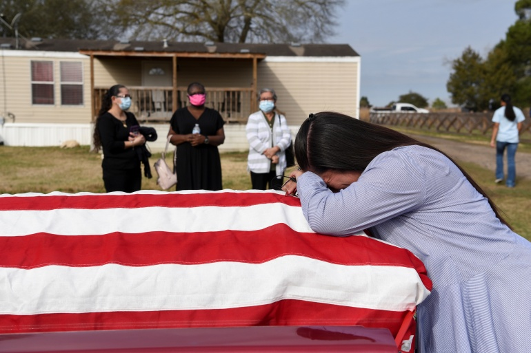 Lila Blanks reacts next to the coffin of her husband, Gregory Blanks, 50, who died from complications from COVID-19, before his funeral in San Felipe, Texas, on January 26 [File: Callaghan O'Hare/Reuters]