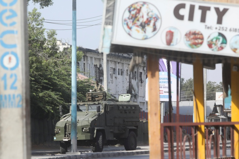 An armoured personnel carrier drives on a street which is sealed off to prevent protests in Mogadishu [Feisal Omar/Reuters]