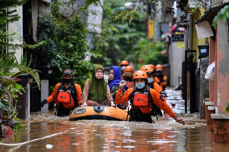Relawan mengevakuasi wanita lanjut usia dengan perahu karet di daerah yang terkena banjir, menyusul hujan lebat di Jakarta, Indonesia [Antara Foto / Sigid Kurniawan via Reuters]