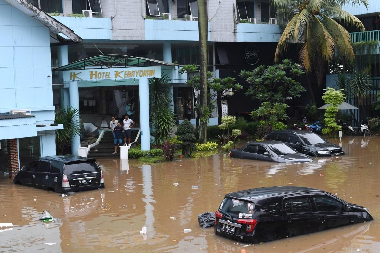 Banjir datang pada saat Indonesia sudah bergulat dengan beban kasus dan penghitungan kematian tertinggi di Asia Tenggara akibat COVID-19, serta kemerosotan ekonomi yang tajam.  [Wahyu Putro / Antara Foto melalui Reuters]