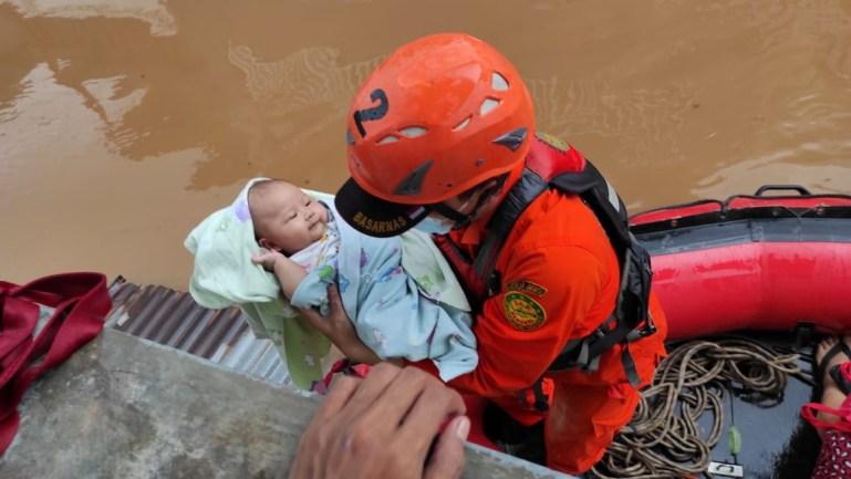 Personel Badan Pencarian dan Penyelamatan Indonesia (Basarnas) mengevakuasi bayi di area yang dilanda banjir.  [Handout: Badan Pencarian dan Penyelamatan Indonesia melalui Reuters]