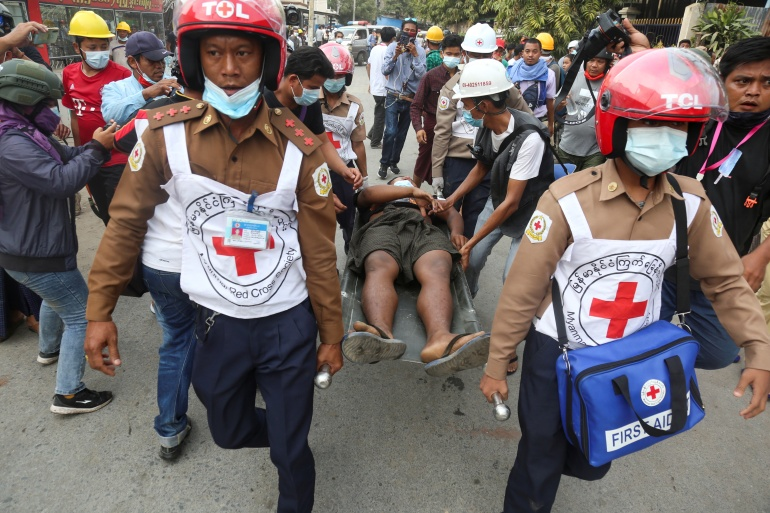 Rescue workers carry a wounded man in Mandalay [Reuters]