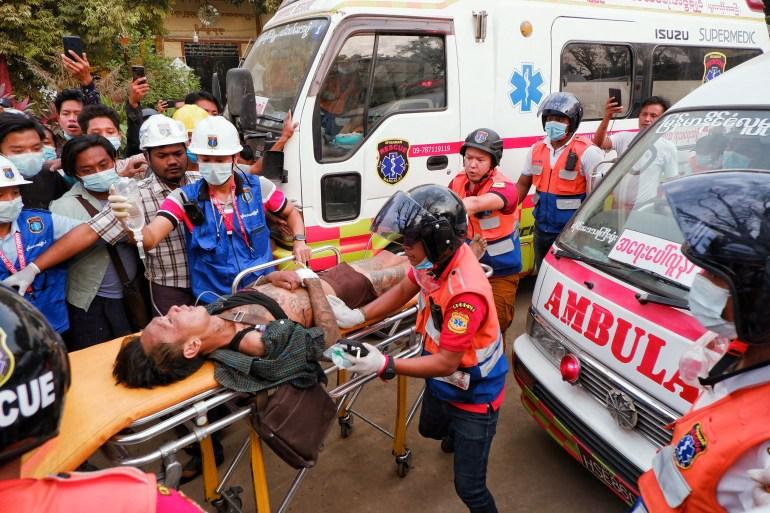 Спасатели несут раненого после протестов против военного переворота в Мандалае, Мьянма, 20 февраля 2021 г. [Stringer / Reuters]