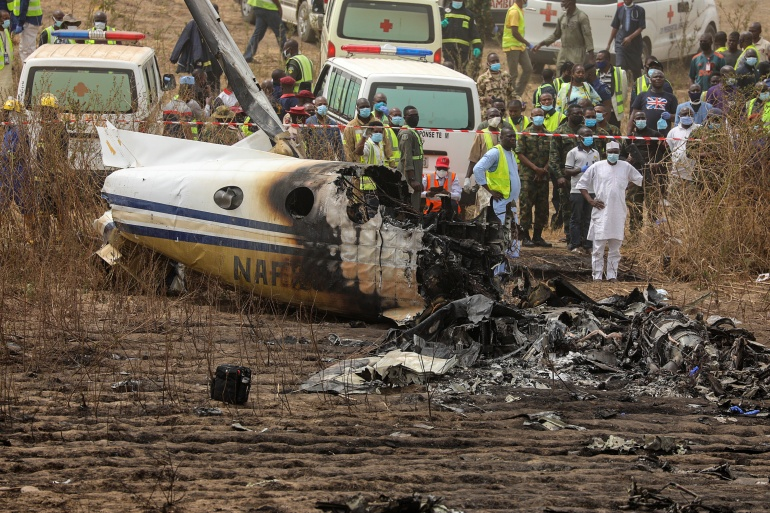 Rescuers and people gather near the debris of the plane [Afolabi Sotunde/Reuters]