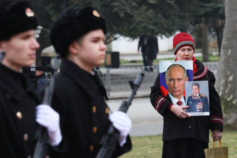 A woman holds portraits of Russian President Vladimir Putin and Defence Minister Sergei Shoigu during celebrations of the Defender of the Fatherland Day in Sevastopol, Crimea on February 23, 2021 [Alexey Pavlishak/Reuters]