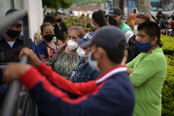 People wait outside the offices of the Forensic Medicine and Forensic Science Institute in Guayaquil. [Vicente Gaibor del Pino/Reuters]
