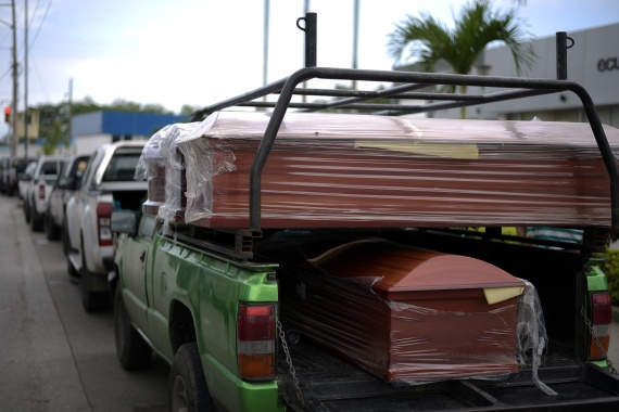 Coffins outside the offices of the Forensic Medicine and Forensic Science institute in Guayaquil, as the bodies of several inmates who died after a prison riot are brought in. [Vicente Gaibor del Pino/Reuters]