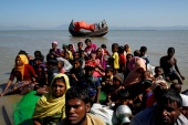 Rohingya refugees sit on a makeshift boat after crossing the Bangladesh-Myanmar border, at Shah Porir Dwip near Cox's Bazar, Bangladesh [File: Navesh Chitrakar/Reuters]