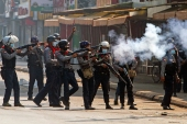 Riot police fire tear gas canisters during protests against the military coup in Yangon [Reuters]