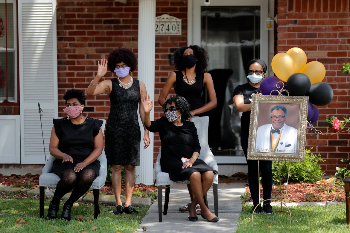 The family of Larry Hammond wave as a line of cars with friends and family - who could not attend his funeral because of the coronavirus - pass by their home in New Orleans on April 22, 2020. [Gerald Herbert/AP Photo]