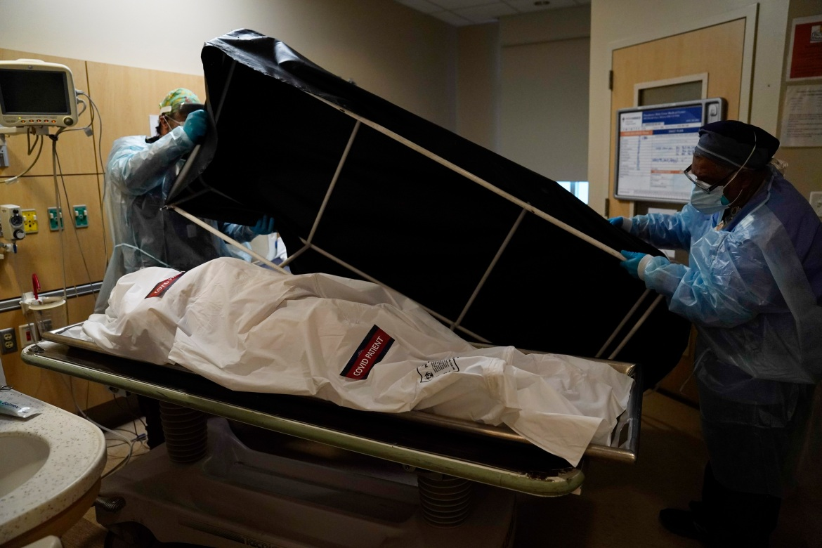 Miguel Lopez, right, and Noe Meza prepare to move a body of a COVID-19 victim to a morgue at Providence Holy Cross Medical Center in the Mission Hills section of Los Angeles on January 9, 2021. [Jae C. Hong/AP Photo]