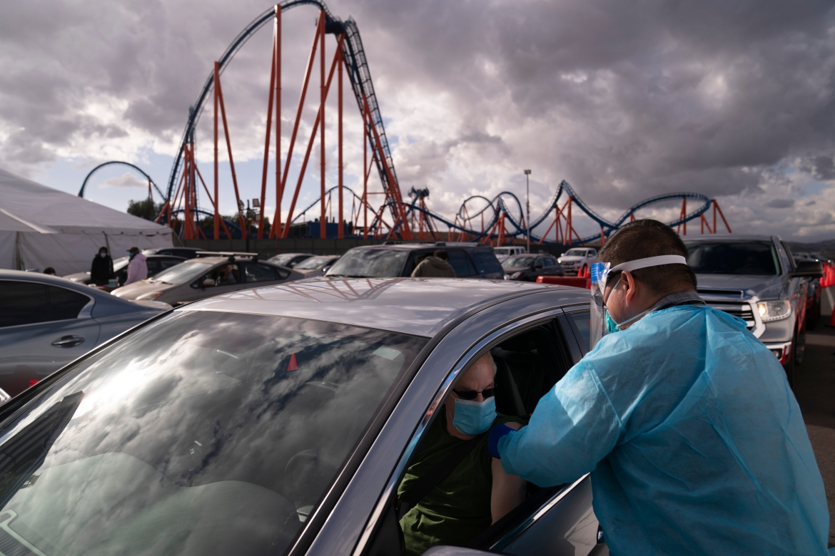 Nurse Joselito Florendo administers the COVID-19 vaccine to Michael Chesler at a mass vaccination site set up in the parking lot of Six Flags Magic Mountain in Valencia, California on January 22, 2021. [Jae C Hong/AP Photo]