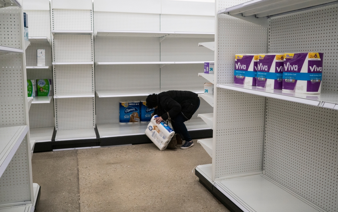 Deanna Butts reaches for one of the last packages of toilet paper at a grocery store in the Tenleytown area of Washington on March 17, 2020. [Carolyn Kaster/AP Photo]