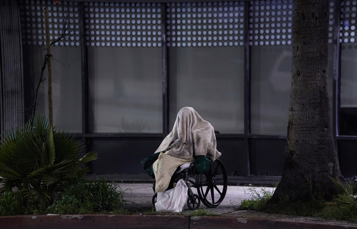 A homeless person sits on a wheelchair under the rain on Sunset Boulevard in the Echo Park neighbourhood of Los Angeles on April 6, 2020. Homeless people are particularly vulnerable to contracting and spreading the coronavirus. [Damian Dovarganes/AP Photo]