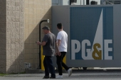 Pedestrians walk past a Pacific Gas and Electric sign in San Francisco. The company faces another legal challenge to a $13.5bn settlement with more than 80,000 Northern California victims worried they are being short-changed [File: Jeff Chiu/AP Photo]