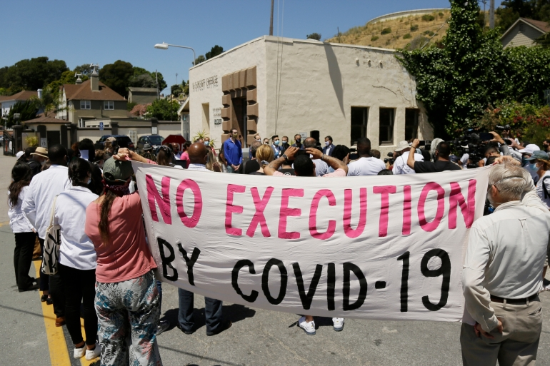 People hold up a banner while listening to a news conference outside San Quentin State Prison in California after a coronavirus outbreak in the facility in July 2020 [File: Eric Risberg/AP Photo]