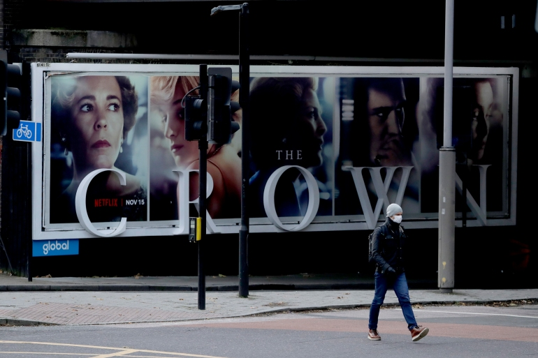 A man wearing a face mask walks past a billboard advertising The Crown, a Netflix drama about the British royal family [File: Matt Dunham/AP]