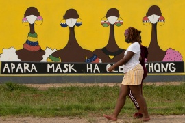 A woman walks past a coronavirus-themed mural promoting the use of face mask in public place, in Sebokeng, Vereeniging, South Africa, Thursday, January 28, 2021 [Themba Hadebe/ AP]