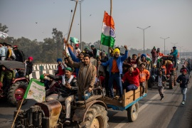 Protesting farmers ride tractors and shout slogans as they march to the capital breaking police barricades during India's Republic Day celebrations [File: Altaf Qadri/AP]
