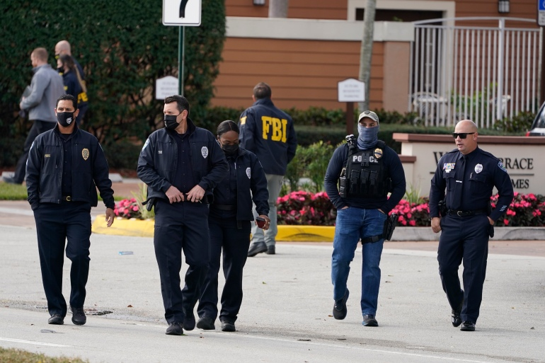 Law enforcement officers walk near the entrance to an apartment complex where a shooting wounded several FBI agents while serving an arrest warrant [Marta Lavandier/AP Photo]