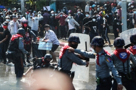 People run after police fire warning-shots and use water cannons to disperse protesters in Mandalay [AP Photo]