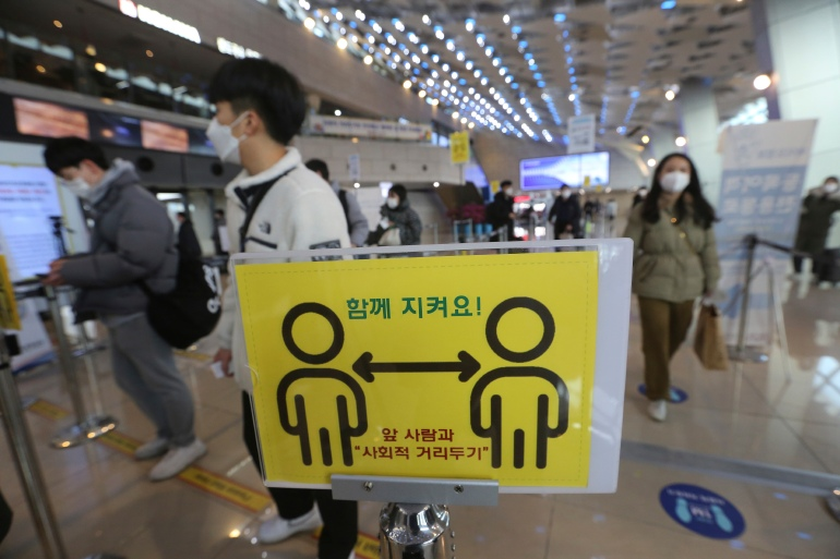A social distancing sign is seen as passengers wait to board planes on the eve of Lunar New Year holiday at the domestic flight terminal of Gimpo airport in Seoul, South Korea, Thursday, February 11, 2021. The signs read: 'Keep together'. [Ahn Young-joon/ AP]
