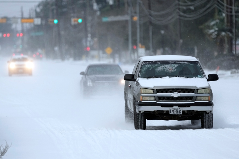 Vehicles drive on snow and sleet-covered roads on Monday, February 15, 2021, in Spring, Texas [File: David J Phillip/AP Photo]