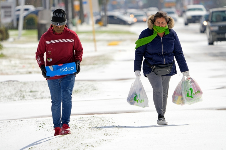 Lia Ubidia, right, and her son, Andrew Velarde, carry groceries as they walk home through the snow Monday, February 15, 2021, in Houston [David J Phillip/AP Photo]