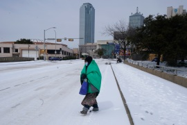 A woman wrapped in a blanket crosses the street near downtown Dallas, on Tuesday, February 16, 2021 (AP Photo/LM Otero) (AP Photo)
