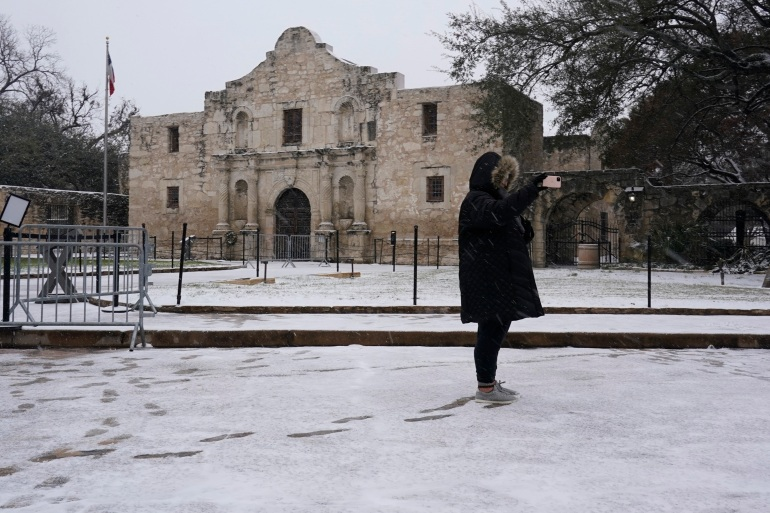 A woman takes a selfie as snow falls over the Alamo, February 18, 2021, in San Antonio, Texas [Eric Gay/AP Photo]