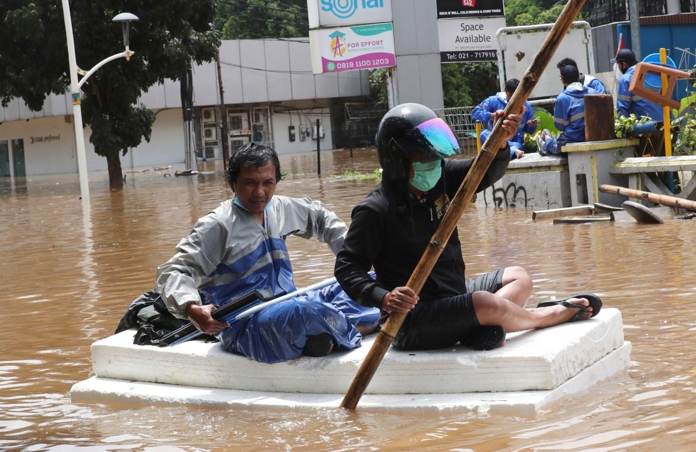 Penduduk menggunakan rakit buatan sendiri untuk melewati jalan yang banjir.  [Foto Tatan Syuflana / AP]
