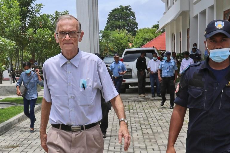 Seorang petugas polisi mengawal Richard Daschbach, mantan misionaris dari Pennsylvania, setibanya di pengadilan di sebuah pengadilan di Oecusse, Timor Leste [Raimundos Oki / AP]