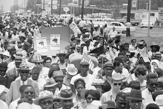 Marchers enter Jackson, Mississippi as part of the March Against Fear on June 26, 1966; two protesters hold signs of the Black Panther party that read 'Move on over or we'll move on over you' [Charles Kelly/AP Photo]