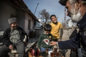 Taufeeq, 55, a Syrian refugee, serves hot black tea to his Uighur neighbour outside his home in Kayseri, Turkey, as his son Moaaz and other children return after playing football [Ahmer Khan/Al Jazeera]